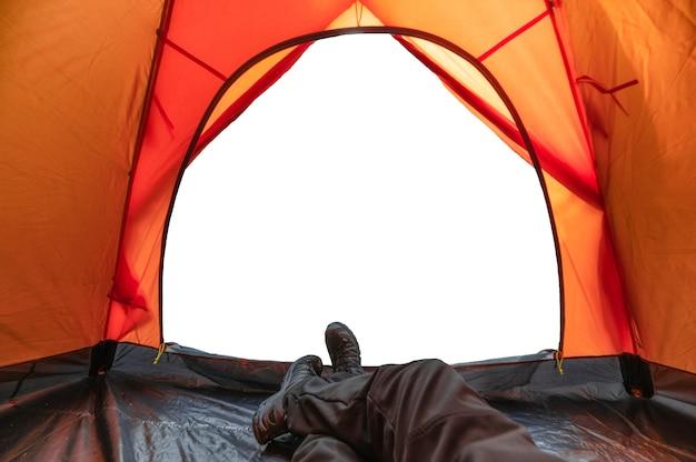 주황색 텐트 안에서 휴식을 취하는 여행자 남자. 몽타주 빈 흰색 배경