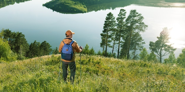 Traveler man standing at lake in mountains. travel lifestyle hiking adventure concept. banner.