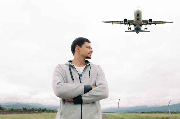 Traveler man stands and looks the airplane taking off