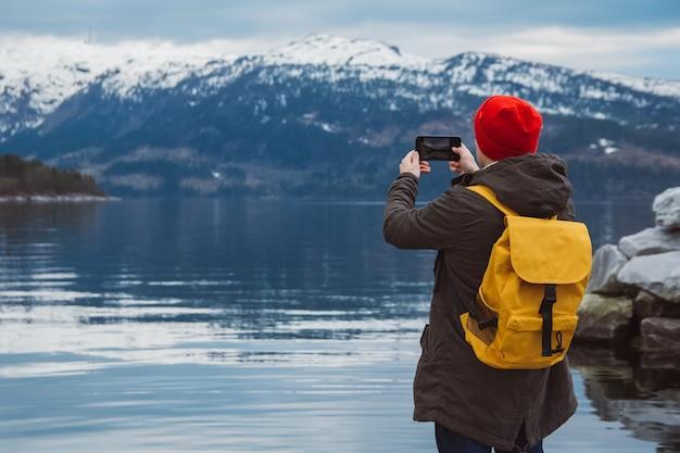 뒤에서 보기를 배경으로 스마트폰을 들고 사진을 찍는 여행자