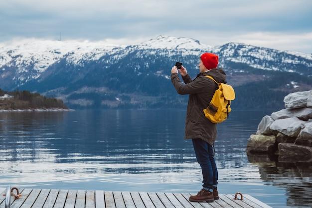 산과 호수 배경의 나무 파이 위에 스마트폰을 들고 사진을 찍는 여행자