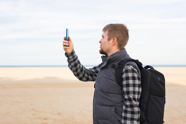 夏の旅行休暇やハイキングでスマートフォンのカメラでビーチに写真を撮る旅行者の男性