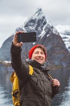 산을 배경으로 스마트폰을 들고 셀카를 찍는 여행자
