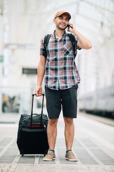 Путешественник разговаривает по телефону на вокзале