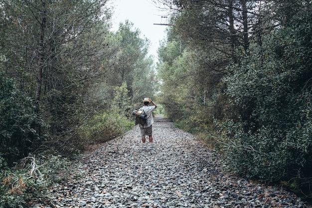 放棄された線路を歩く旅行者の男