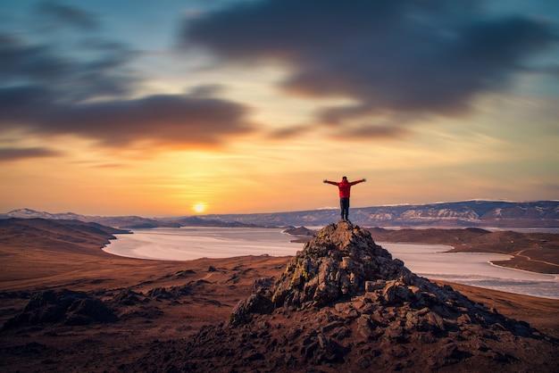 旅行者の男性は赤い服を着て、ロシア、シベリアのバイカル湖の日没時に山に立って腕を上げます。