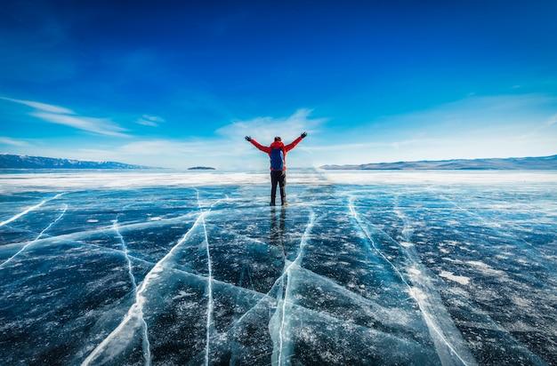 旅行者の男性は赤い服を着て、ロシアのシベリアのバイカル湖で凍った水の自然な砕氷の上に立って腕を上げています。