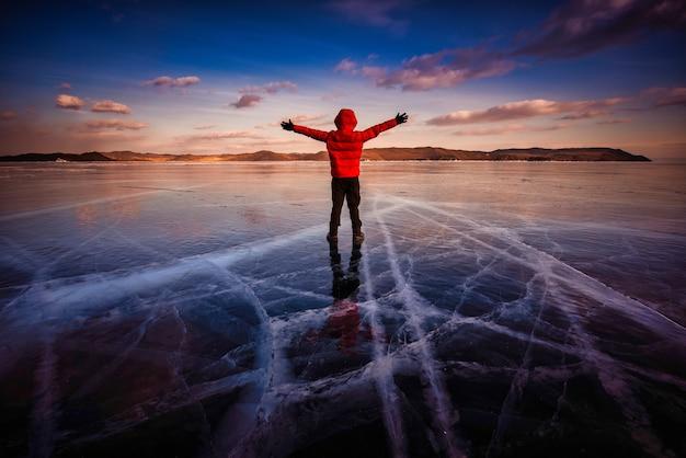Путешественник в красной одежде и поднимает руку, стоя на естественном ломающемся льду в замерзшей воде у озера байкал, сибирь, россия.