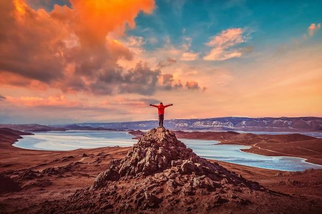 Человек-путешественник в красной одежде и поднимающей руку стоит на вершине горы возле озера байкал, сибирь, россия.