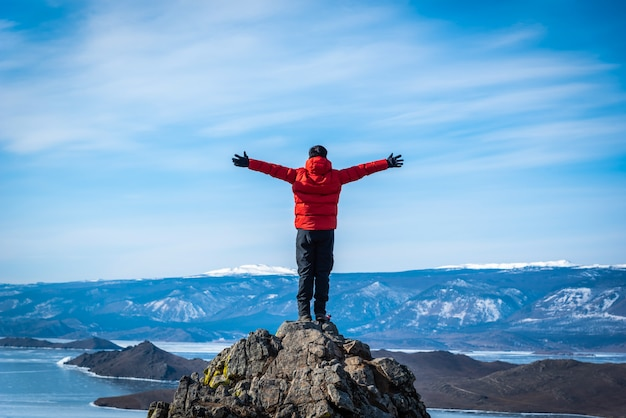 Traveler man wear red clothes and raising arm standing on mountain at daytime in lake baikal, siberia, russia.