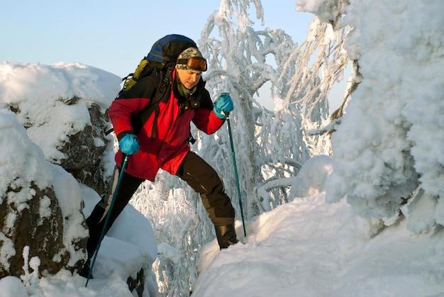 美しい冬の山の風景の中でバックパックを持った旅行者の男は絶壁を越えます