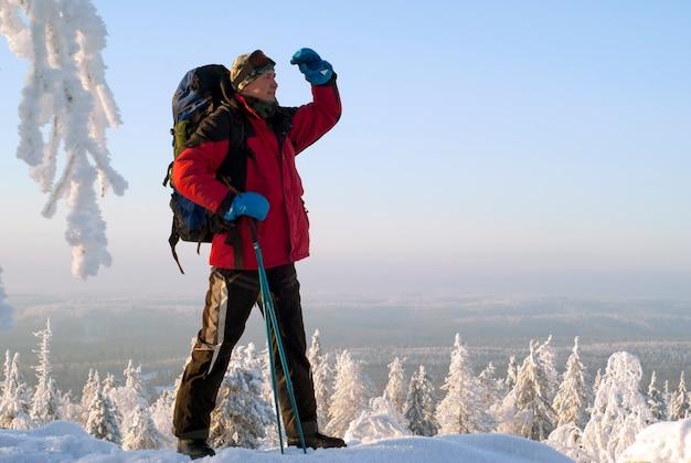 山の上に立っている腕の下から遠くを見ているバックパックを持つ旅行者の男