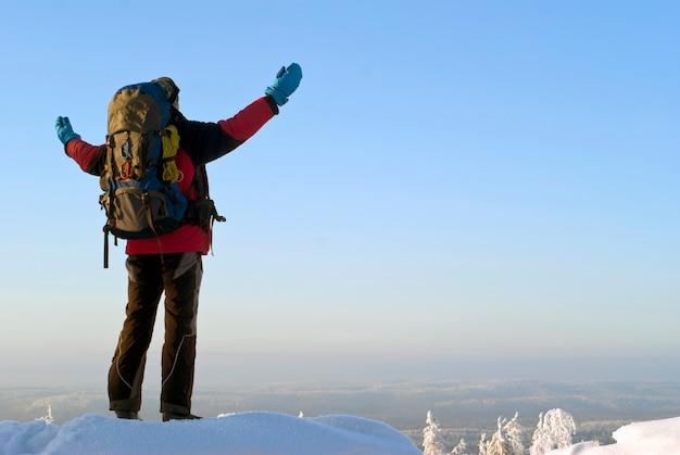 冬の山の頂上にバックパックを背負った旅行者の男が腕を広げ、景色を眺める