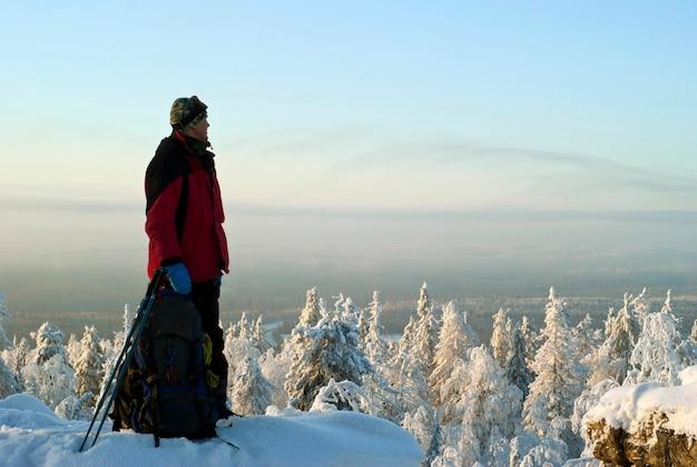冬の山にバックパックを背負った旅人が景色を眺めながら小道を振り返る