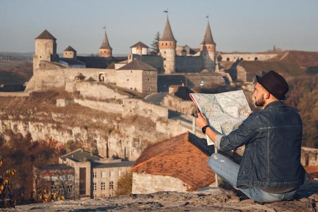 手に地図を持つ旅行者の男は、古い城の背景に座っています
