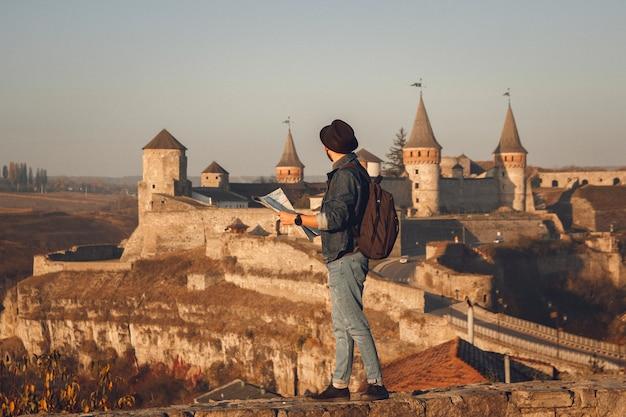 手に地図を持つ旅行者の男は、古い城の背景に立っています