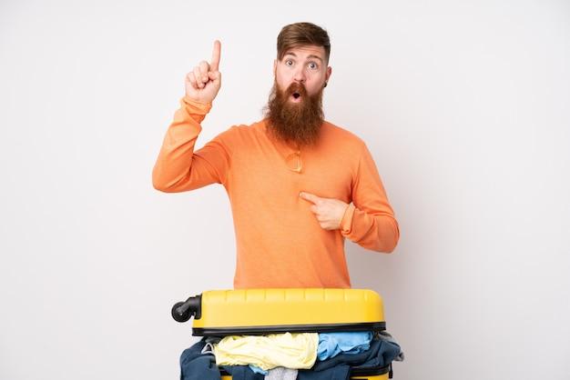 Человек путешественника с чемоданом, полным одежды над изолированной белой стеной с удивленным выражением лица