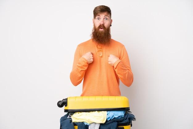 勝利を祝っている白い壁の上の服でいっぱいのスーツケースを持つ旅行者男