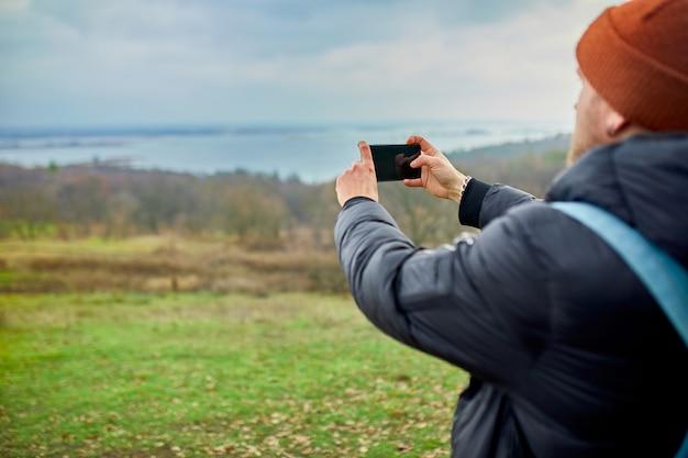 バックパックを持つ旅行者の男性は、スマートフォンで写真やセルフィーを、川や山のある携帯電話、ライフスタイルを作ります。
