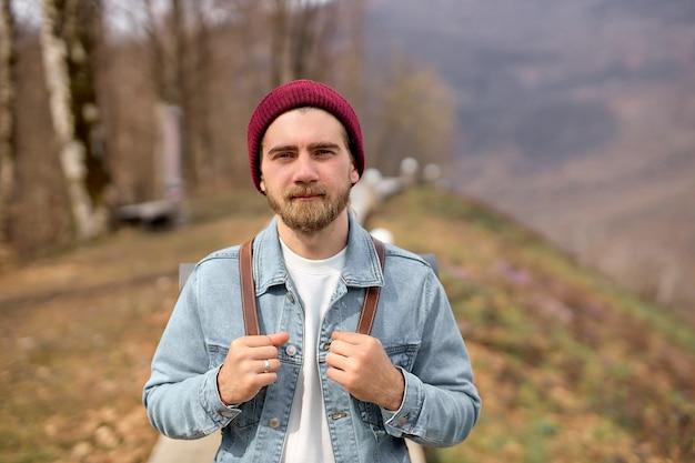 自然の中で一人で歩くバックパックを持つ旅行者の男。自由の概念。コピースペース