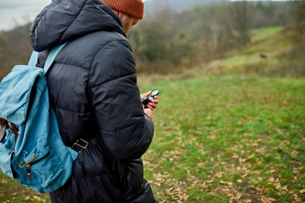 Путешественник с рюкзаком с компасом в руке на фоне гор природы