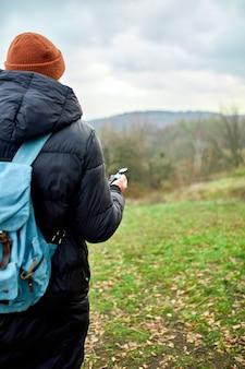 자연의 산 강, 여행 개념, 캠핑 여행, gps, 오리엔티어링, 네비게이터의 벽에 손에 나침반 배낭 여행자 남자