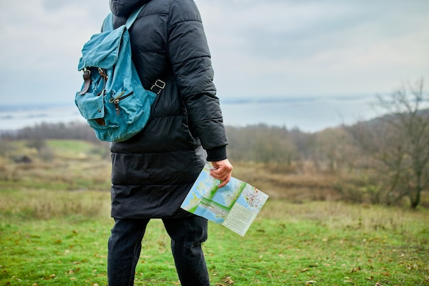 Путешественник с рюкзаком с картой в руке на фоне горной реки природы