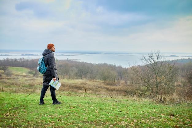 自然の山川に地図を持ったバックパックを持つ旅行者の男性、旅行のコンセプト、休暇、ライフスタイルのハイキングのコンセプト