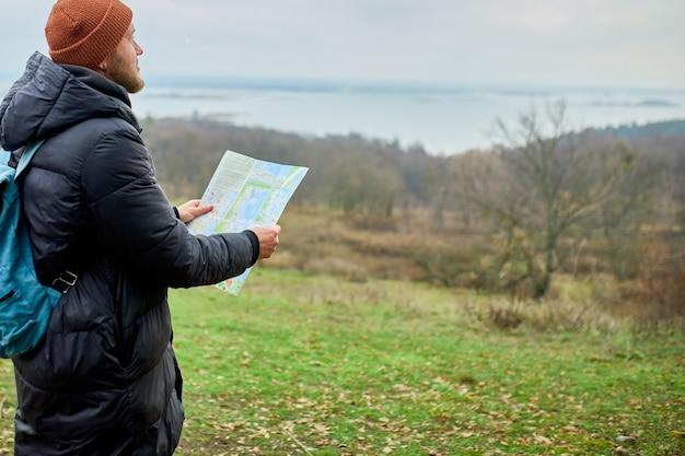 自然の山の川でポーズをとる地図を手にバックパックを持つ旅行者の男性、旅行のコンセプト、休暇、ライフスタイルのハイキングのコンセプト