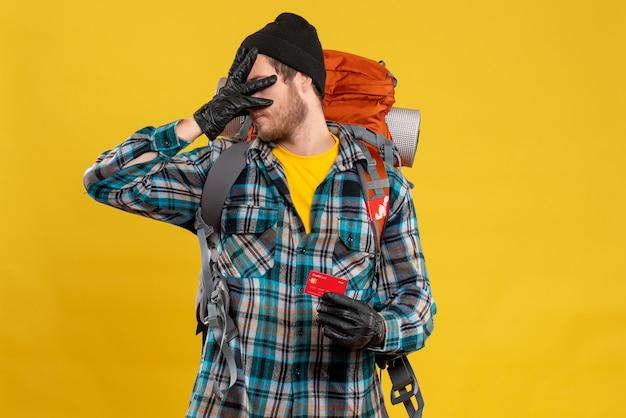 バックパッカーと頭を抱えたカードを持つ旅行者の男性