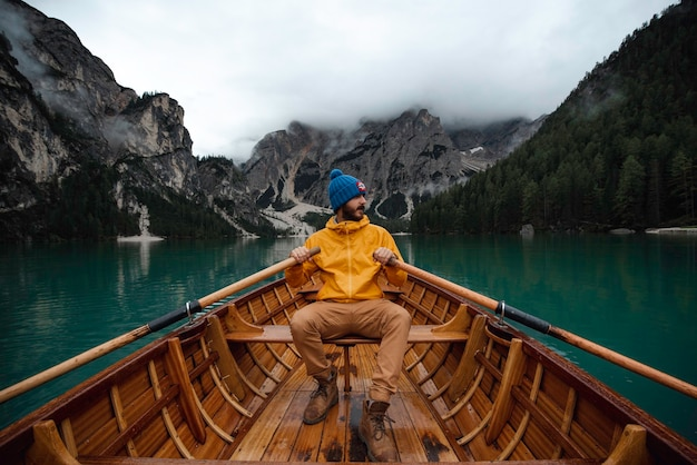 Traveler man with blue hat and yellow raincoat sailing in a wooden boat through a beautiful di braies lake in the dolomites mountains.
