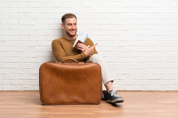 Traveler man with suitcase and boarding pass pointing to the side to present a product