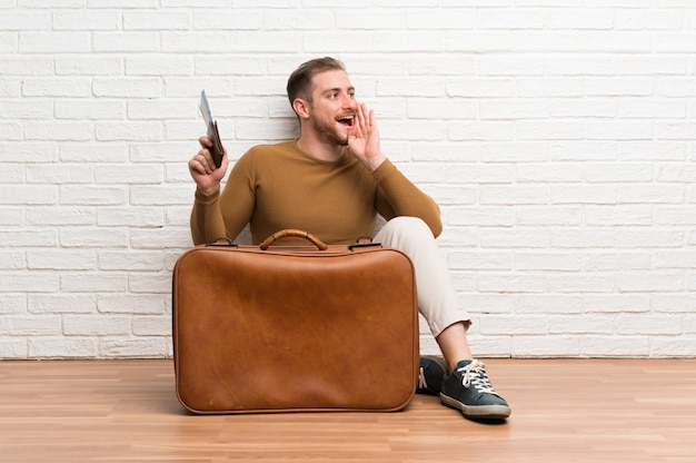 Traveler man with suitcase and boarding pass shouting with mouth wide open