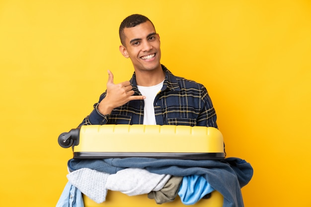 Traveler man with a suitcase full of clothes over isolated yellow wall making phone gesture