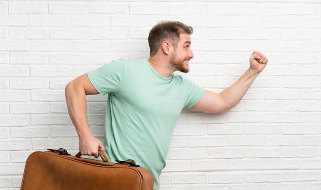 レンガの壁と高速実行のスーツケースを持つ旅行者男