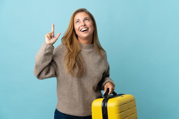 여행 가방과 함께 휴가에 파란색에 고립 된 가방을 들고 가리키는 여행자 중년 여자