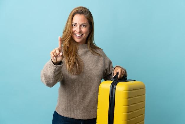 旅行スーツケースと1つを数えて休暇で青い壁に分離されたスーツケースを保持している旅行者の中年女性