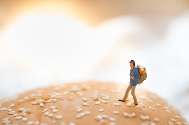 Traveler minature figure toy walking on top of beef burger.