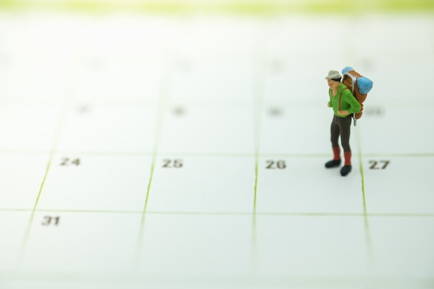 Traveler miniature figure people with backpack standing on calendar