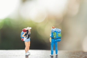 Traveler miniature people with backpack stand and walking