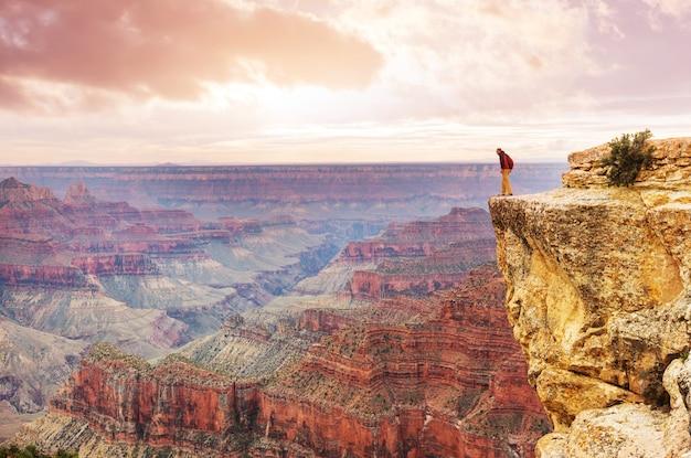 Путешественник на скалах над национальным парком гранд-каньон, аризона, сша. вдохновляющие эмоции. путешествие образ жизни путешествие концепция мотивации успеха приключения отдых на открытом воздухе концепция.