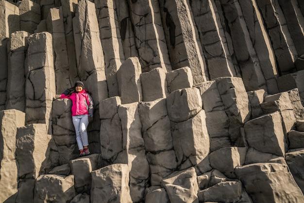 Путешественник на шестиугольных скалах в vik, исландия.