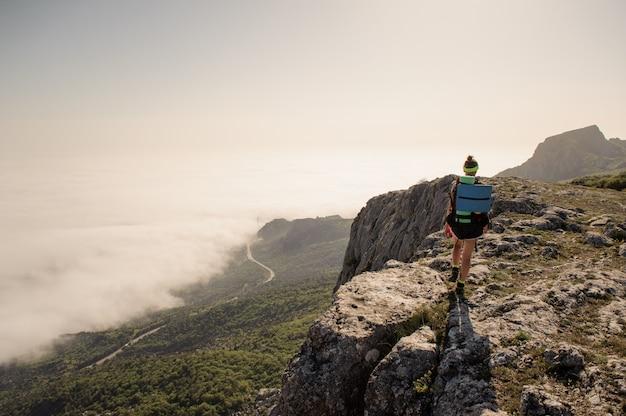 山の上の旅行者。スタイリッシュな女性のハイキング。大気の瞬間