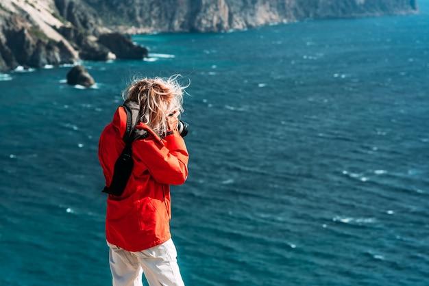 빨간 재킷을 입은 여행자 사진가가 카메라, 후면 보기에 바다 경치의 사진을 찍고 있습니다. 배경 바다에 사진 카메라에 사진 바다 풍경을 만드는 관광 여행자 사진 작가. 복사 공간