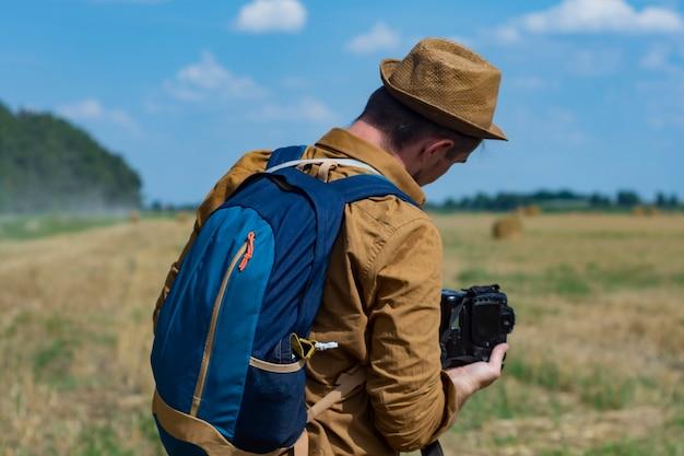 들판과 건초 더미를 배경으로 카메라를 들고 있는 여행자 사진가.