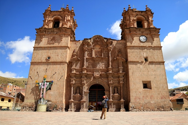 Traveler photographing the cathedral basilica of st. charles borromeo or cathedral of puno, peru