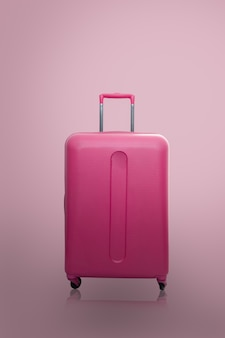 Traveler pink suitcase or cabin size luggage on pink background, travel concept