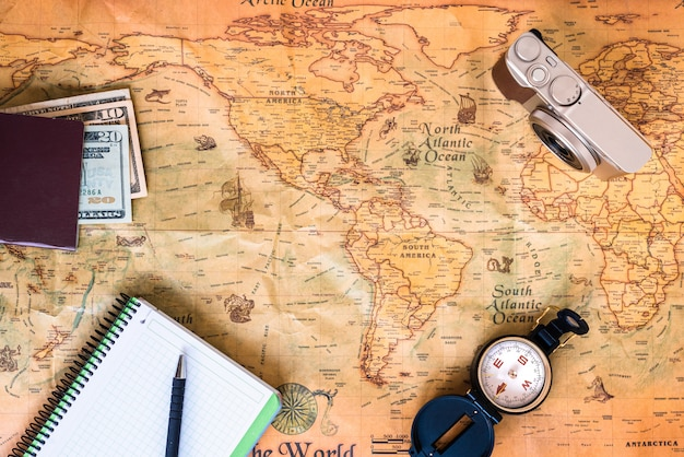 A traveler plans his trip around the world on an old map, while taking notes to get inspired.