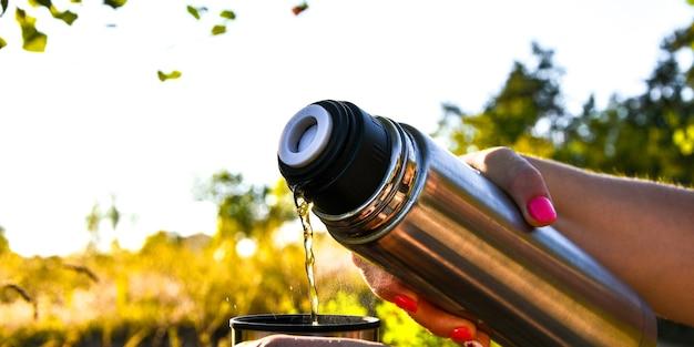 屋外の秋の倒れた森で魔法瓶からカップに熱いお茶を注ぐ旅行者。夏秋のピクニック。コピースペース