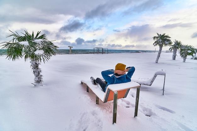 Путешественник отдыхает на шезлонге среди вечнозеленых тропических пальм, покрытых снегом